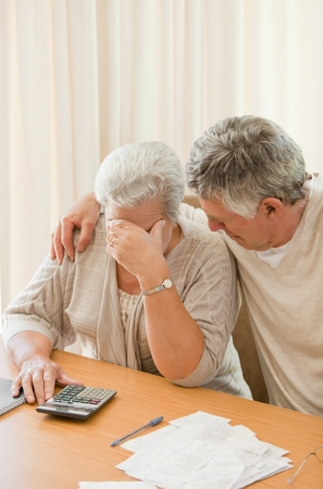 Sad mature couple calculating their domestic bills photo