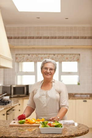 Retired woman looking at the camera in the kitchen photo