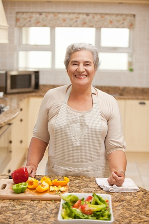 Retired woman looking at the camera in the kitchen Stock Photo - 10194465