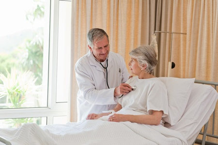 hospital stress: Senior doctor taking the heartbeat of his patient