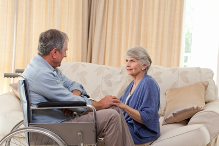 amputation: Senior couple talking in the living room at home