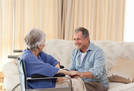 female senior adults: Senior couple talking in the living room at home
