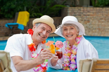 getaway: Happy senior couple drinking cocktail and toasting each other