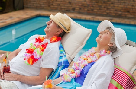 Retired couple sleeping beside the swimming pool photo