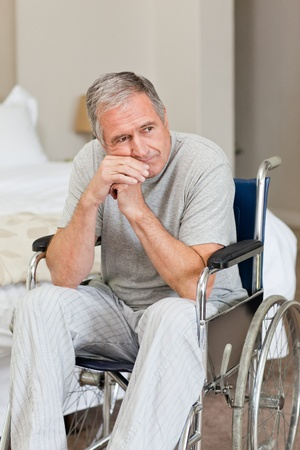 Worried senior man in his wheelchair  at home photo