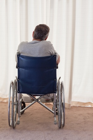 Mature man in his wheelchair with his back to the camera photo