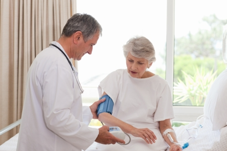Mature doctor taking the blood pressure of his patient photo