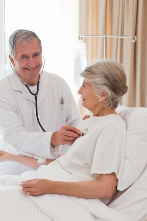 Doctor taking the heartbeat of his patient Stock Photo - 10218810