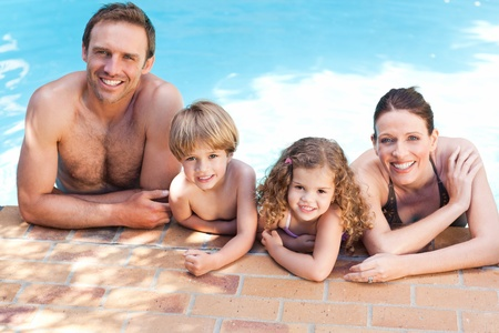 Happy family beside the swimming pool photo