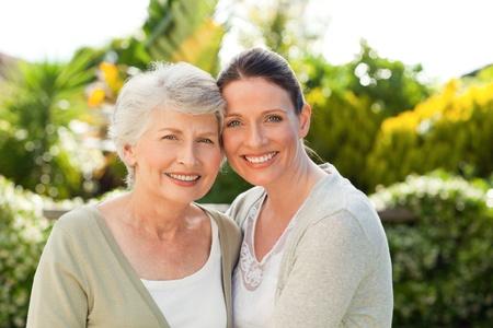 mother and daughter: Madre con su hija mirando la cámara en el jardín