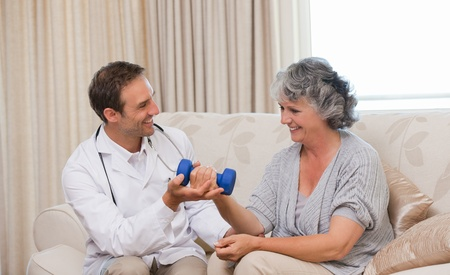 Handsome doctor helping his patient to do exercises photo