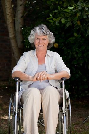 paraplegico: Mujer sonriente en su silla de ruedas Foto de archivo