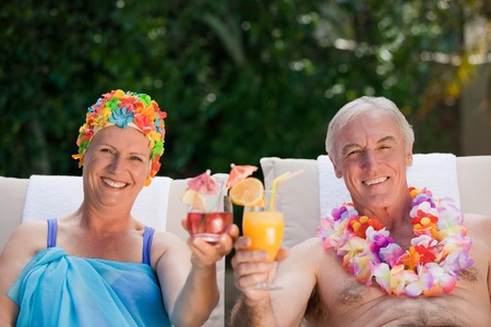 Mature couple drinking a cocktail  beside the swimming pool Stock Photo - 10173861