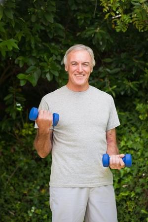 Senior man doing his exercises in the garden photo