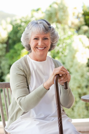 leans: Retired woman with her walking stick Stock Photo