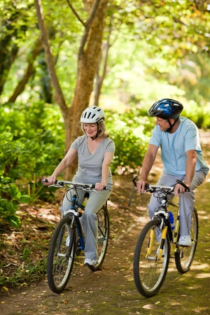 Elderly couple mountain biking outside photo