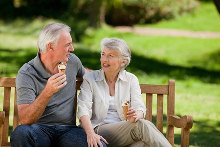Senior couple eating an ice cream on a bench photo