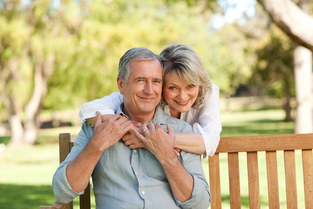 mid adult couples: Senior woman hugging her husband who is on the bench Stock Photo