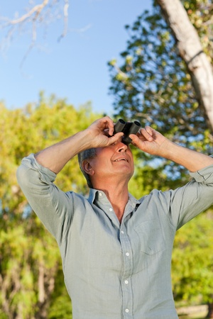 Senior man looking at the sky with his binoculars photo