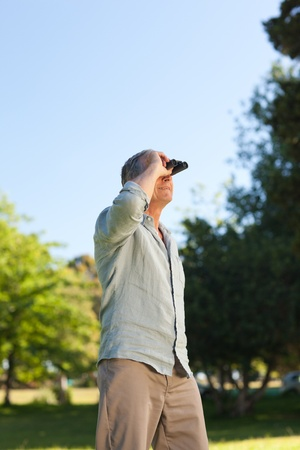 Elderly man looking at the sky with his binoculars photo