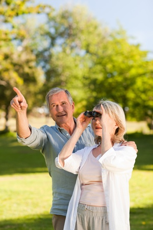 facing away: Couple looking at the sky with their binoculars