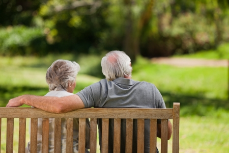 old man smiling: Couple sitting on the bench  with their back to the camera Stock Photo