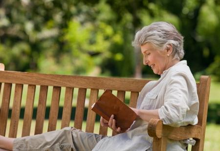 jubilados: Jubilada de leer un libro en el banco