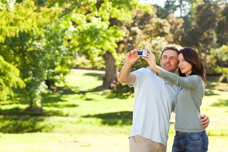 Couple taking picture of themselves in the park photo