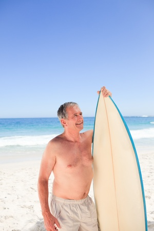 Senior man with his surfboard photo
