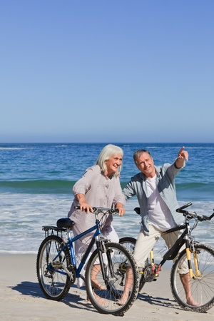 Mature couple with their bikes on the beach photo