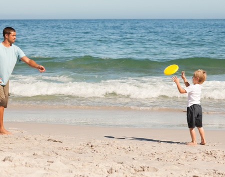 Little boy playing frisbee with his father photo