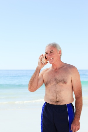 Senior man listening to his shell Stock Photo - 10170462