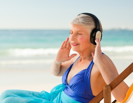 Retired woman listening to music at the beach photo