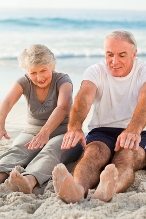 Couple doing their streches at the beach photo