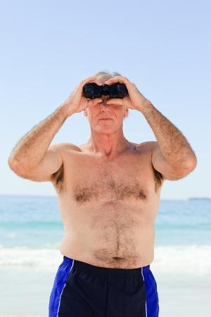 Senior man bird watching at the beach photo