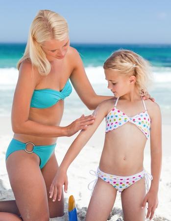 beach model: Mother applying sun cream on her daughter