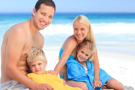 Parents with their children in their towels photo