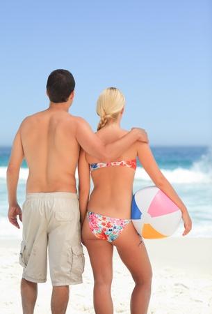 Woman huging her husband on the beach photo