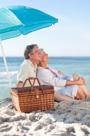 active holiday: Elderly couple picniking on the beach