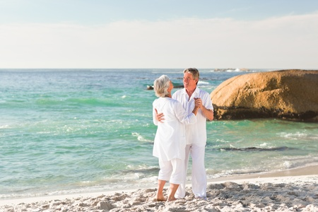 active holiday: Retired couple dancing on the beach Stock Photo