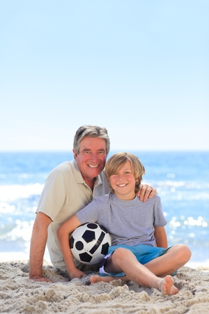 union beach: Grandfather and his grandson with a ball