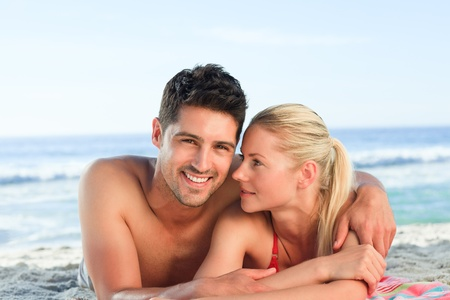 Lovers lying down on the beach photo