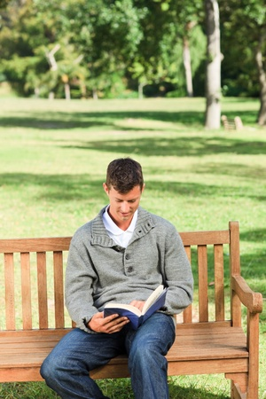 Young man reading his book on the bench photo