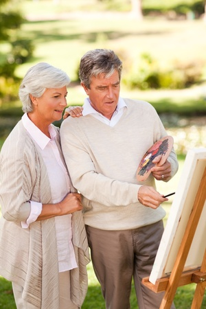 Retired couple painting in the park photo