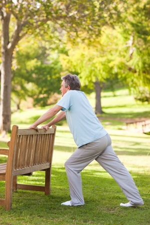 Retired man doing his stretches in the park photo
