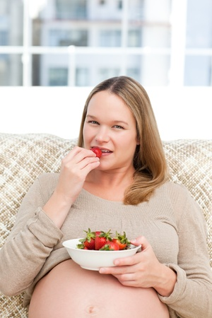 Serious future mom eating strawberries sitting on the sofa photo