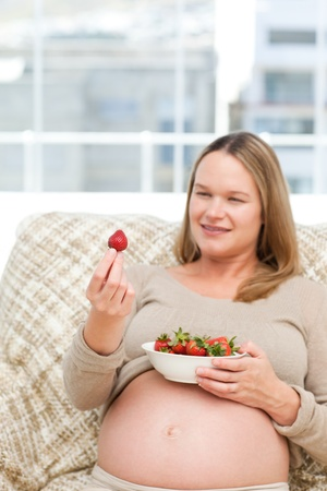 Adorable pregnant woman looking at a strawberry while relaxing photo