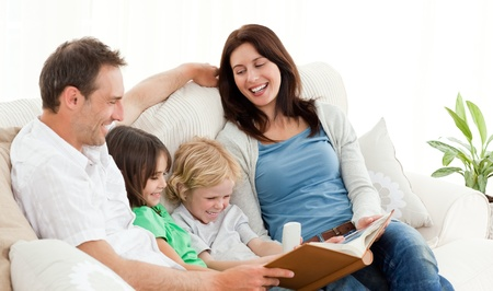 family memories: Happy parents looking at a photo album with their children Stock Photo