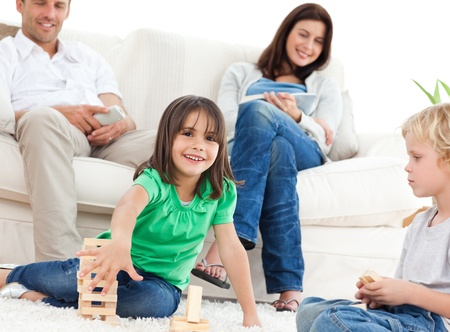 Happy children playing with dominoes in the living room  photo