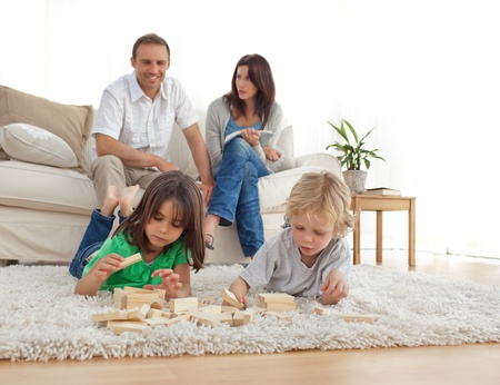 mamá hijo: Padres felices en el sofá mirando sus niños jugando en el piso